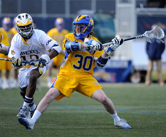 Delaware freshman Connor Frisina (Conestoga) scores one of his two goals in Saturday's 11-10 loss to Drexel as Clifton Simeon defends (Photo by Tim Flatley)
