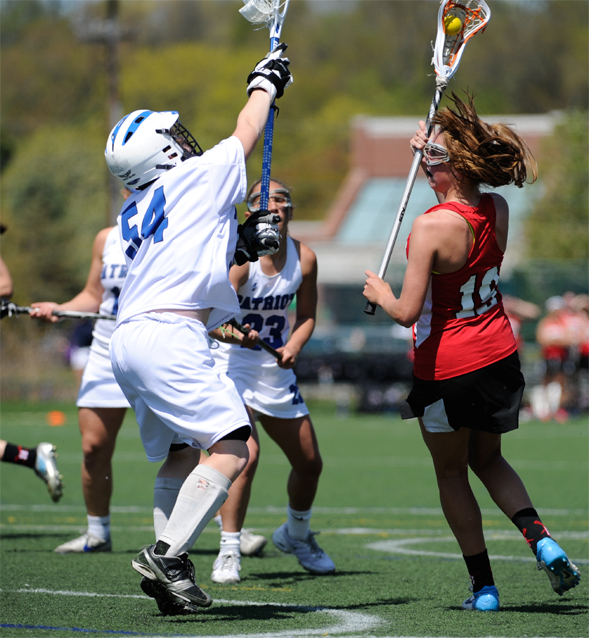 Harriton's Jane Henderson scores one of her three goals in Saturday's 15-13 win over Great Valley. Playing goal is Merrilee Viguers (Photo by Tim Flatley)