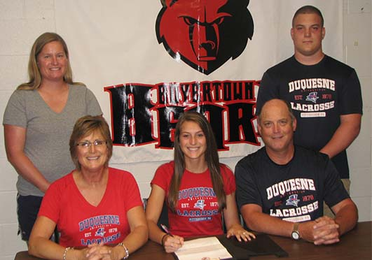 Boyertown senior Kaitlyn DeHaven, flanked by parents Carol and Brian DeHaven, signs a national letter of intent to accept an athletic scholarship to play Division I lacrosse at Duquesne University during a recent ceremony at the high school. Also on hand for the signing were Boyertown coach Pam Wernersbach and brother Jake DeHaven.