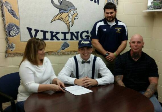 Mikey signs with parents and Coach Brady McCormick