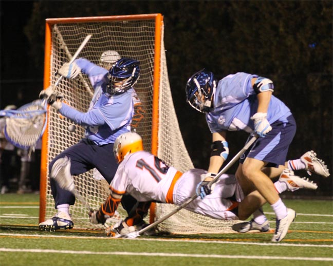 FORMER TEAMMATES COLLIDE - Princeton attackman Ryan Ambler dives to the goal with UNC's Austin Pifani defending during Friday's game. Both played at Abington High. (Photos by Rene Schleicher)