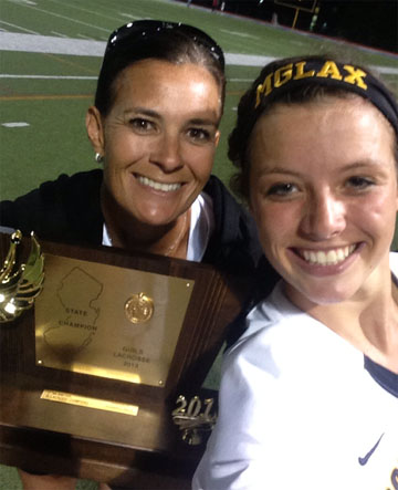 Moorestown (NJ) coach Deanna Knobloch (left) accepts the New Jersey Tournament of Champions trophy with goalie Shannon Keeler in 2013.