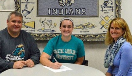 Upper Perkiomen senior Regan McComb, flanked by father Bill McComb and Upper Perkiomen coach Susan Flack, signs a national letter of intent to accept a Division I lacrosse scholarship from Coastal Carolina during a recent ceremony at the high school. (Photo courtesy of Upper Perk athletics via PAC-10Sports.com)
