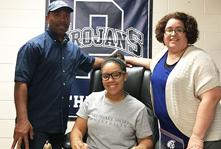 Pottstown senior Sabrina Butler, seated between parents Kenny and Wanda Butler, makes a verbal commitment to continue her academic and lacrosse career at Delaware Valley College during a recent ceremony at the high school.